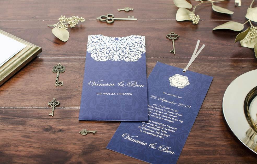 Elegante Hochzeitsdeinladung in Blau mit barockem Ornament in Gold der Serie Vanessa und Ben von carinokarten