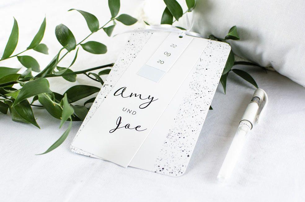 Moderne Hochzeitseinladung mit schwarzen Sprenkeln als Kartenset mit kleinen Anhängern in Mint  aus der Serie Amy und Joe von carinokarten
